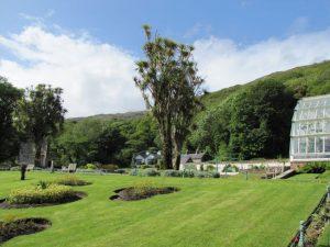 Gereinigte friedliche Natur - Garten mit großem Gewaechshaus und bewaldeten Bergen im Hintergrund