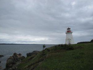 Impressum - Leuchtturm auf einer begrasten Anhöhe im Hintergrund das Meer und viele Wolken am Himmel